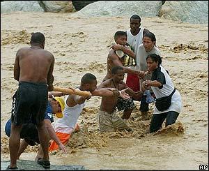 Una familia trata de cruzar un río crecido por las inundaciones.
