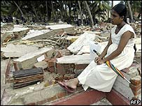 A Sri Lankan woman sits amid the rubble of her house
