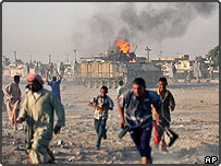 Iraqis run from the area as a British Warrior fighting vehicle burns in Basra