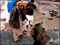 Villagers survey the damage to a road look, caused by torrential rains in Muzaffarabad, capital of Pakistani Kashmir on Friday.