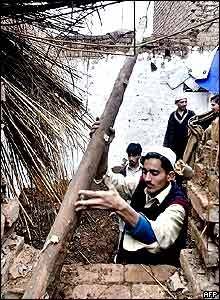 A Pakistani man removes debris from his house which collapsed due to continuous rain as others look on in Peshawar.