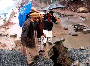 People look at breach on a road, caused by torrential rains in Muzaffarabad, capital of Pakistani Kashmir .