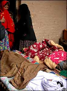 Family members look at dead bodies of children killed by a roof cave-in of their house after continued heavy rain killing four people in Peshawar.