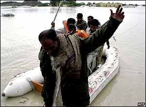 Rescue workers evacuate flood victims from their houses in Aghor, some 270km west of Karachi.