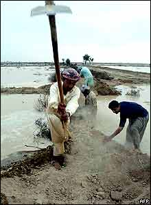 Villagers make an embankment to prevent flood water from entering to their neighbourhood in Aghor, some 270km west of Karachi.