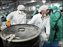 Two technicians carry a box containing yellow cake at the Iranian nuclear facility at Isfahan