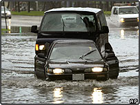 Vehicles drive through flooded streets in Miami Beach, Florida