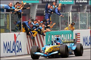 Alonso crosses the finish line in front of his team in Sepang