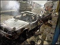 Un soldado de EE.UU. junto a los restos de un auto