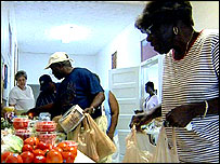 Bernice Beatty (far right) and others collect day-old bread and vegetables at Sister Pat Baber's Catholic charity