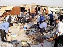 Iraqi policemen search through the rubble that was their station