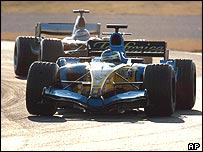 Fernando Alonso's Renault is chased by the McLaren of Kimi Raikkonen in Formula One pre-season testing