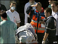 Members of Israel's forensic institute prepare to transport the body of a Palestinian into an ambulance in Tel Aviv