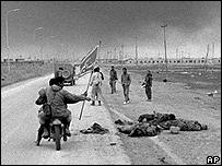 Soldados iraníes pasan junto a militares iraquíes muertos.