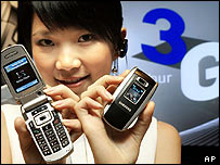 Japanese woman displays 3G mobile phones
