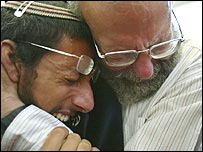 Religious Jewish settlers cry as they walk out of their synagogue in Gaza