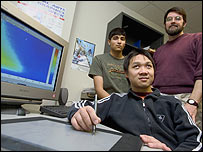Photo of Victor Wong sitting at his computer with James Ferwerda and Ankur Moitra standing behind.  Image courtesy of Cornell University