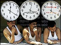 Three men sitting under clocks in Mumbai