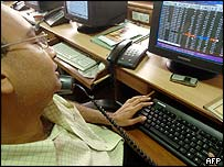 Indian trader sitting in front of his screen and computer