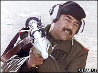 Saddam Hussein firing a rocket propelled grenade