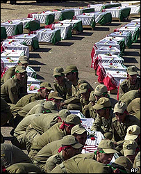 In 2002, Iranian soldiers receive the bodies of 80 Iranians killed in the war