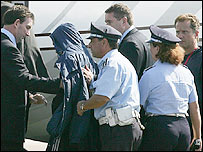 Mr Osman (in blue hood) boarding an aircraft in Rome
