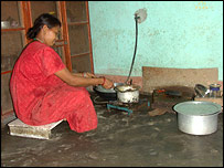 Nepalese woman cooks on single-ring biogas burner.  Image: BSP