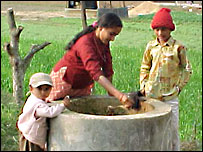 Woman and children mix dung.  Image: BSP