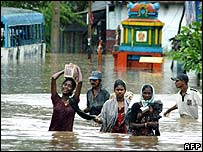 Indian villagers wade through floodwaters in Andhra Pradesh
