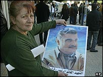 Woman shows martyr's poster showing Rafik Hariri