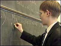 Boy writing French words on blackboard