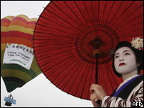 A Japanese girl stands in front of a hot air balloon in Kyoto, Japan.