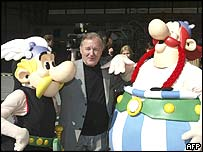 Illustrator Albert Uderzo flanked by models of his characters