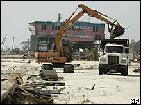 Workers clean debris scattered along the beach front by Hurricane Katrina in Biloxi, Mississippi