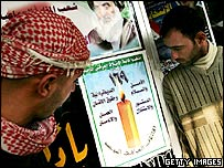 Iraqi men look at poster of poll-winners, the United Iraqi Alliance