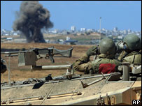 An Israeli tank crew watches an explosion in the Palestinian village of Beit Hanoun, north of the Gaza Strip