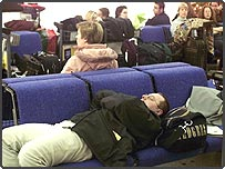 Stranded passengers wait in an airport lounge