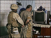 A US soldier takes an Iraqi prisoner in Hit
