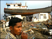 An Acehnese man smokes a cigarette near a house on which a fishing boat landed after it was swept away by tsunami in Banda Aceh, 17 Feb