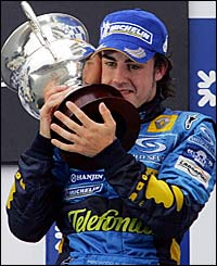 Fernando Alonso cuddles the world championship trophy