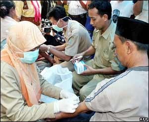 Health workers collect blood samples from the relatives of a woman who died from bird flu in Sempu Gardu village in the Cikarang district, west Java, 26 September 2005.