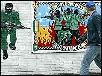 Man walking past IRA mural in Belfast
