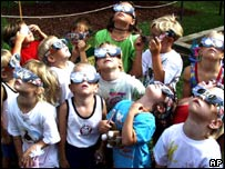 Children in Kapfenberg, Austria peer through eclipse glasses