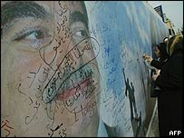 Mourners sign their name on a mural to dead former Lebanese Prime Minister, Rafik Hariri