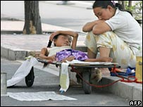 A Beijing woman rests beside her sick child hoping for donations, 27 August 2005