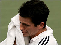 Tim Henman wipes the sweat during a tough tennis match