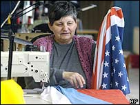 A Slovak woman sews US and Slovakian flags