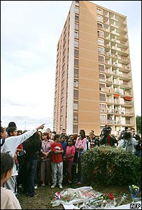 Mourners gather outside the tower block from which the girls jumped