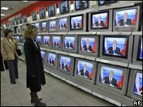 Dos mujeres observan a Vladimir Putin, presidente de Rusia, durante una sesión televisada de preguntas y respuestas