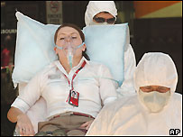 Virgin Airline employee is wheeled from a terminal by paramedics in protective clothing Monday, Feb. 21, 2005.